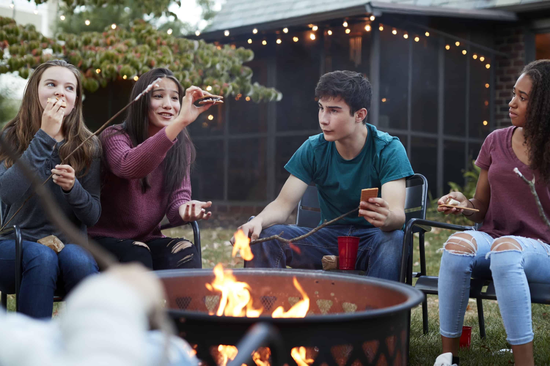 Teenage friends eating sÕmores around a firepit