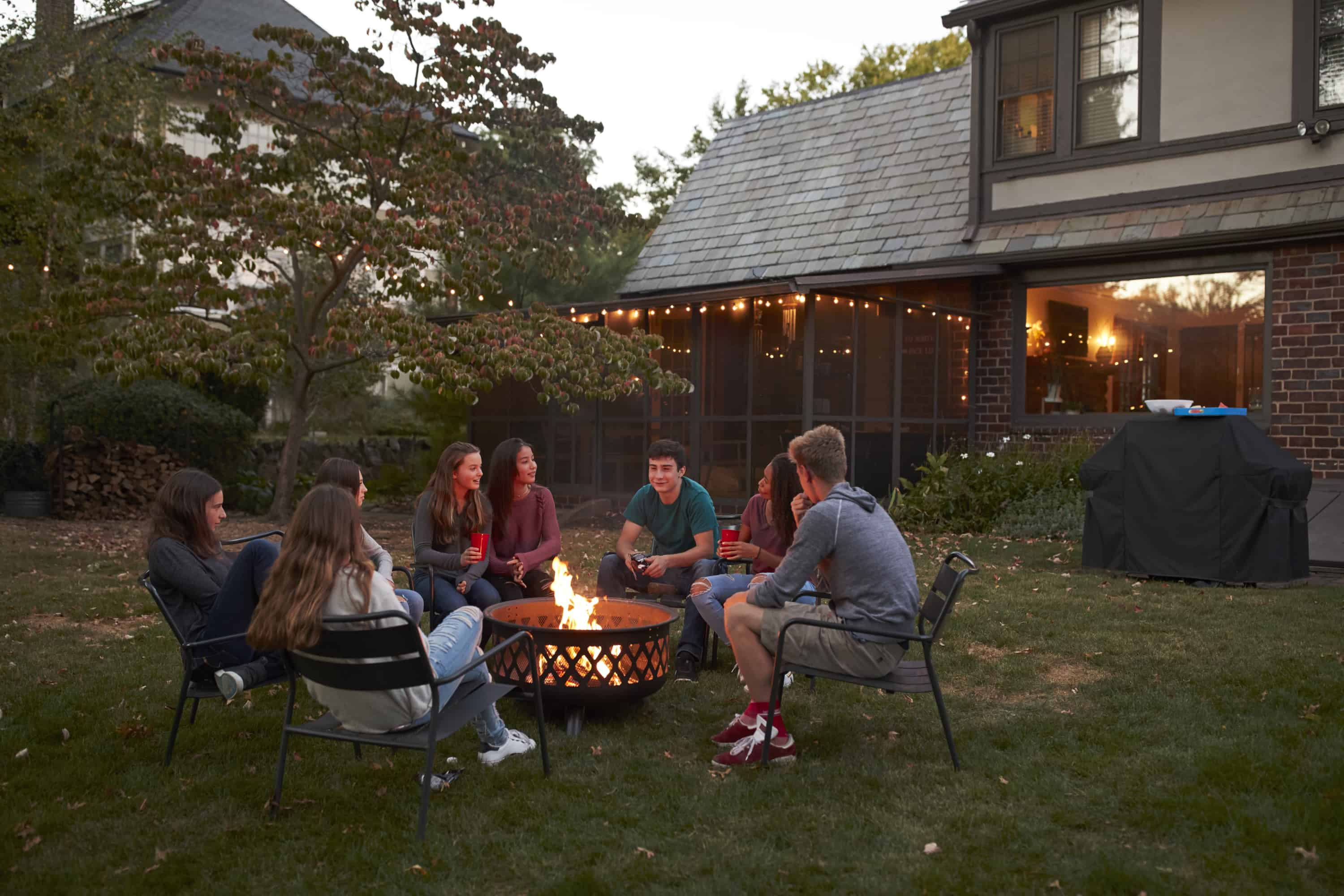 Teenagers sit talking around a fire pit in a garden at dusk